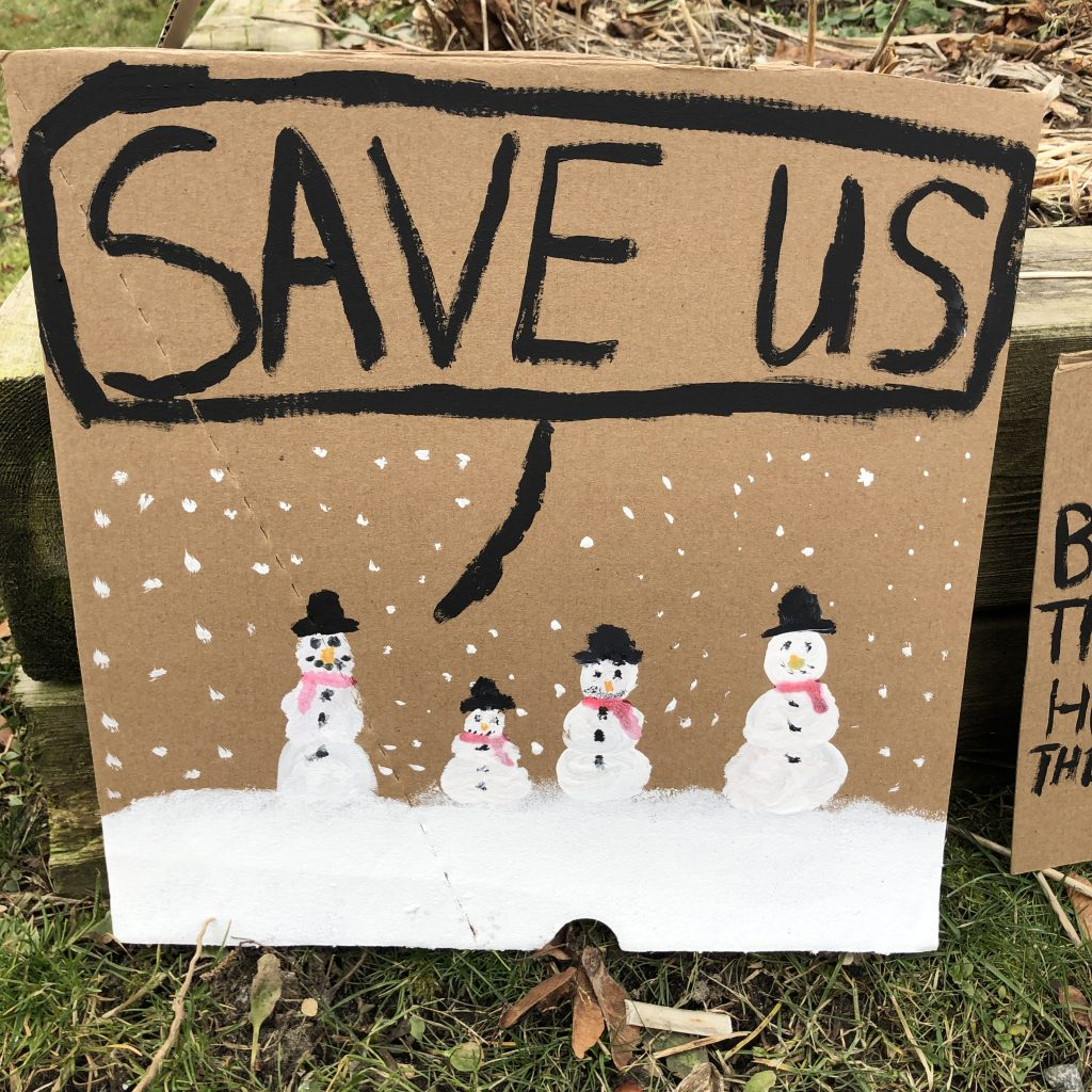 Snowmen saying Save Us: Sign from November 29 climate strike.