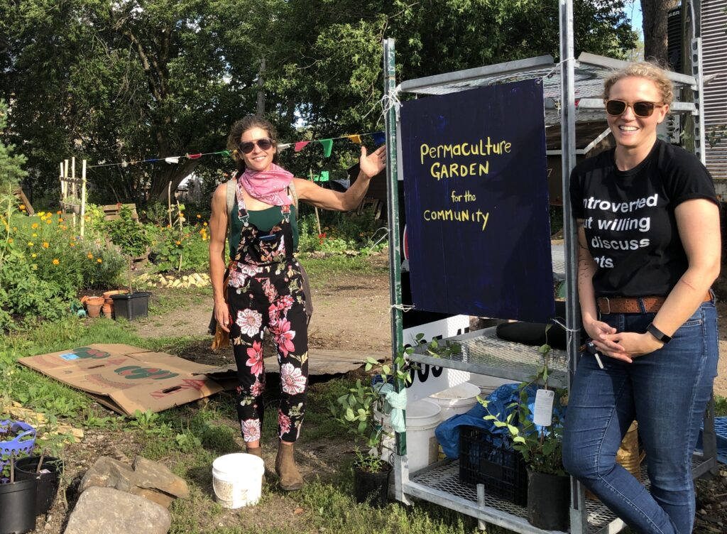 """Picture of Tricia Bilissis and Bet Smith with a sign that says """"Permaculture Garden for the Community."""""""