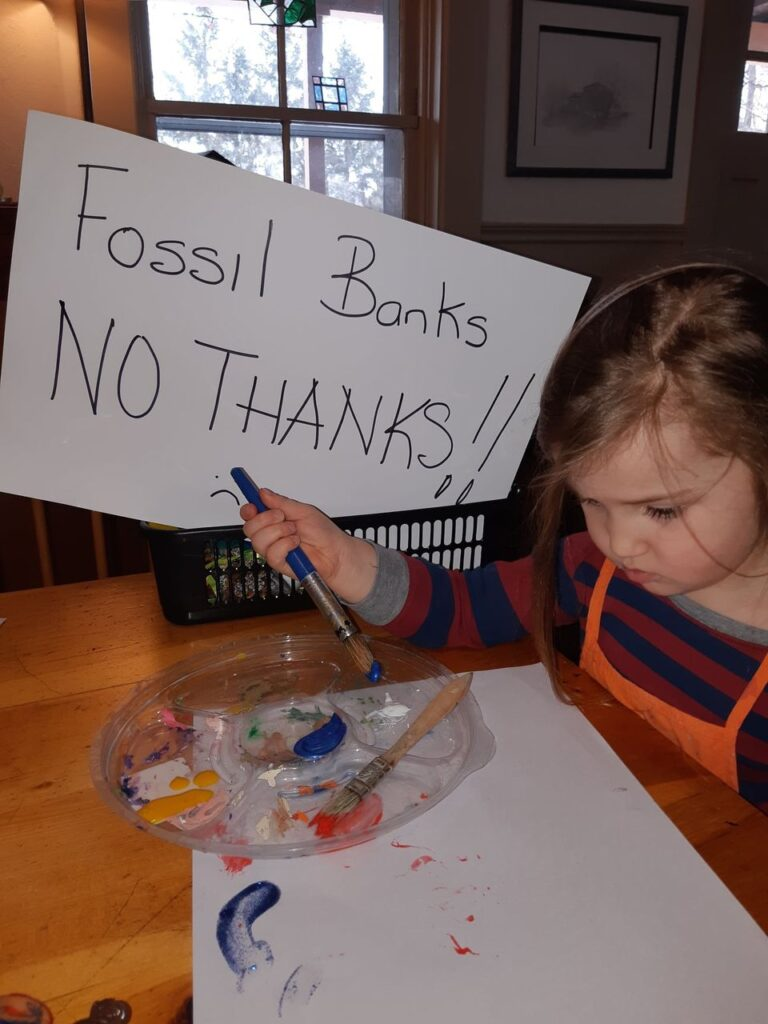 """Picture of Darwen doing art with sign reading """"Fossil Banks No Thanks!!"""""""